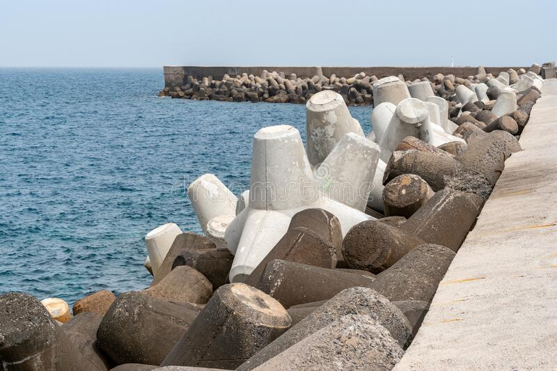 Protección de aguas residuales bajo cielo azul, bloques de hormigón sólido en el puerto de Heraklion Grecia fotos de archivo