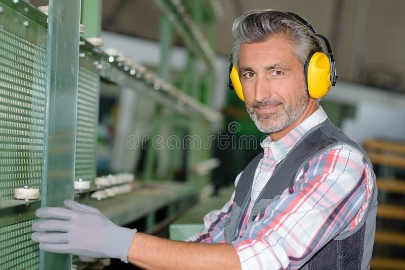 Protección de oído del trabajador que lleva en la fábrica imagen de archivo