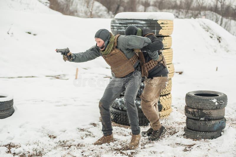 Protección de seguridad del escolta y de la gente del VIP Entrenamiento del tiroteo del arma del combate fotos de archivo libres de regalías