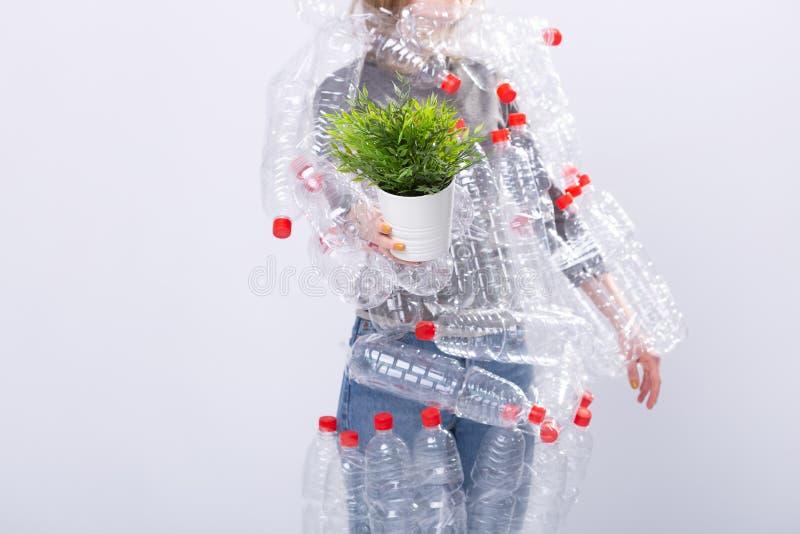 Protección del medio ambiente, gente y concepto plástico reciclable - cierre para arriba de la mujer que sostiene la planta verde foto de archivo