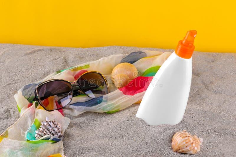 Protección solar con los vidrios y las conchas marinas en la arena en un fondo amarillo imagen de archivo libre de regalías