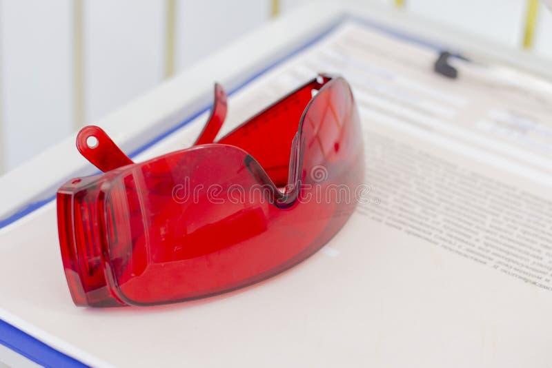 Protección ULTRAVIOLETA de los vidrios rojos protectores en la depilación del laser de la odontología de la cosmetología imagenes de archivo