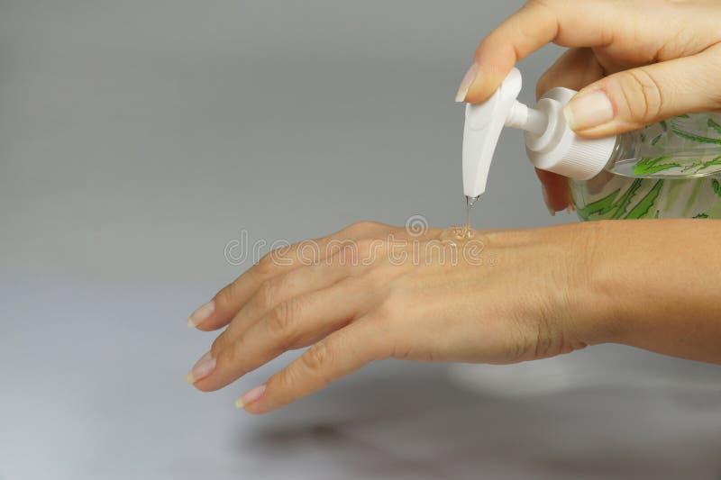 Protección y cuidado El acto de aplicar el cosmético bajo la forma de gel para el cuidado de la mano foto de archivo