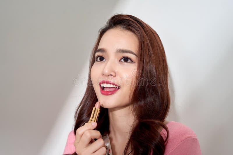 Protecci?n de los labios Mujer hermosa con la cara de la belleza, labios llenos atractivos que aplican el protector labial, palil imagenes de archivo