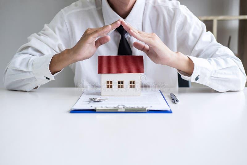 Protecci?n del seguro y del cuidado del concepto de la casa, agente del hombre de negocios con gesto protector del peque?o modelo foto de archivo libre de regalías