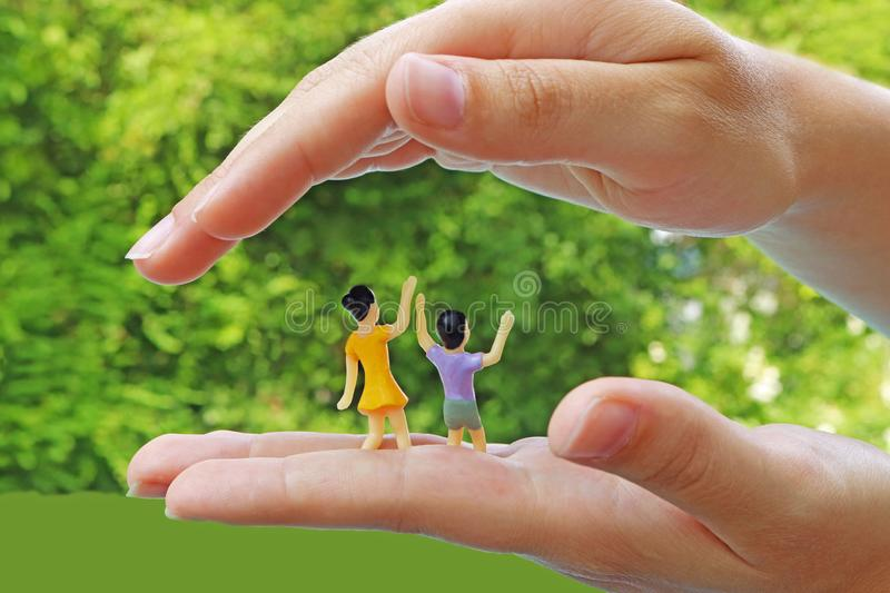 Protect children, symbolic picture with miniature figurines royalty free stock photos