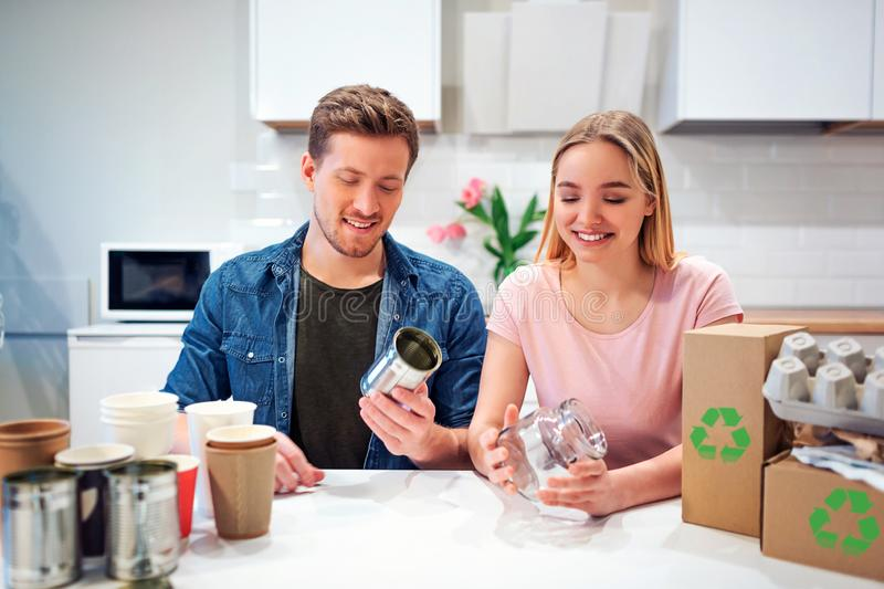 Protect the environment. Young couple recycling metal tin can and glass while sitting at the table with other waste at. Protect the environment. Young couple royalty free stock images