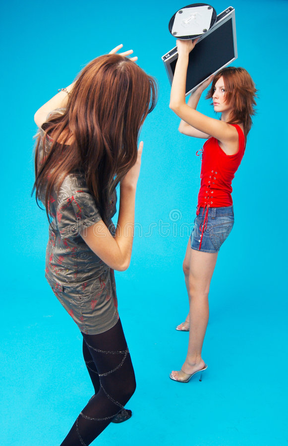 Protect From Monitor As A Weapon. Teenage girl preparing to throw a blank computer monitor over her head at another girl. Her hands are raised up for protection royalty free stock image
