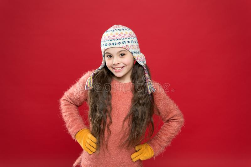 Protect your ears and hair from cold. being in playful mood. kid fashion. Warm knitting. happy little girl in earflap royalty free stock image