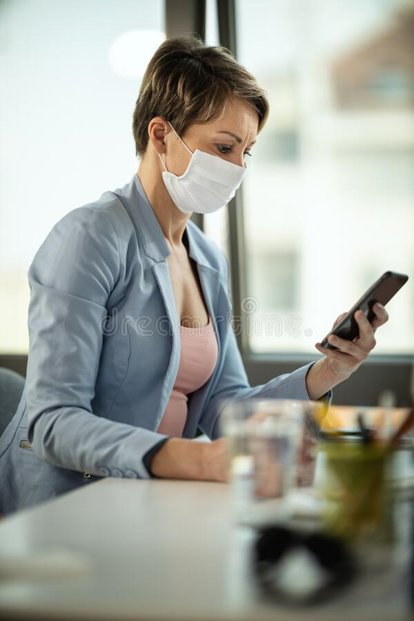 Protect Yourself By Isolation. Business woman in a medical protective mask surfing at social network at the smartphone and works from home, during self-isolation stock photo