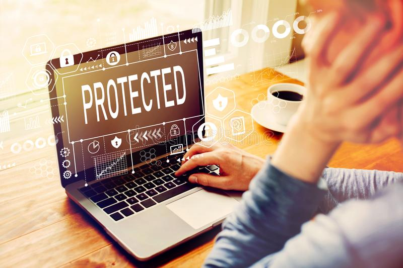Protected with man using a laptop. Computer stock photos