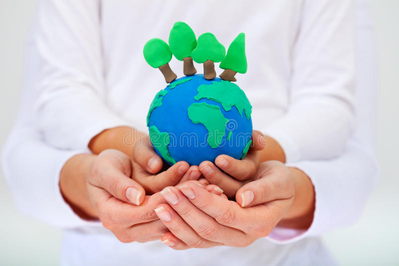 Protecting our environment concept. Clay earth with trees held by child and adult hands royalty free stock photos