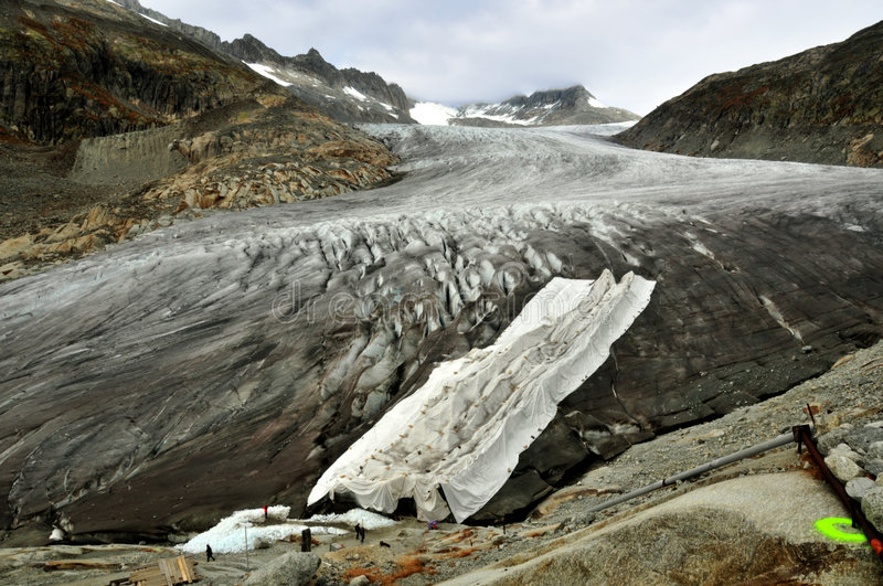 Protecting the Rhone Glacier. White reflective sheets are used to cover glaciers in switzerland to reduce melting, and the reduction of the glaciers caused by royalty free stock image