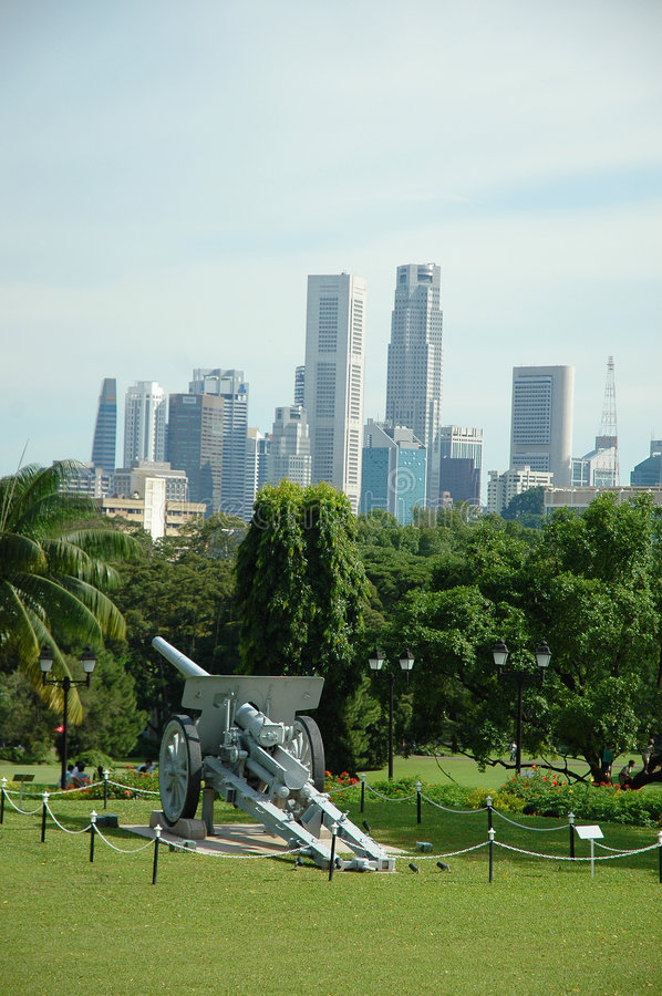 Protecting Singapore. An old artillery canon at the Istana watches over the Singapore skyline, as if protecting it royalty free stock photos