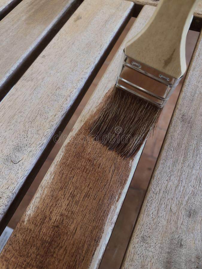 DIY and home improvements, painting furniture. Protecting teak wooden furniture, painting wooden slats with oil, closeup of brush and wood stock images