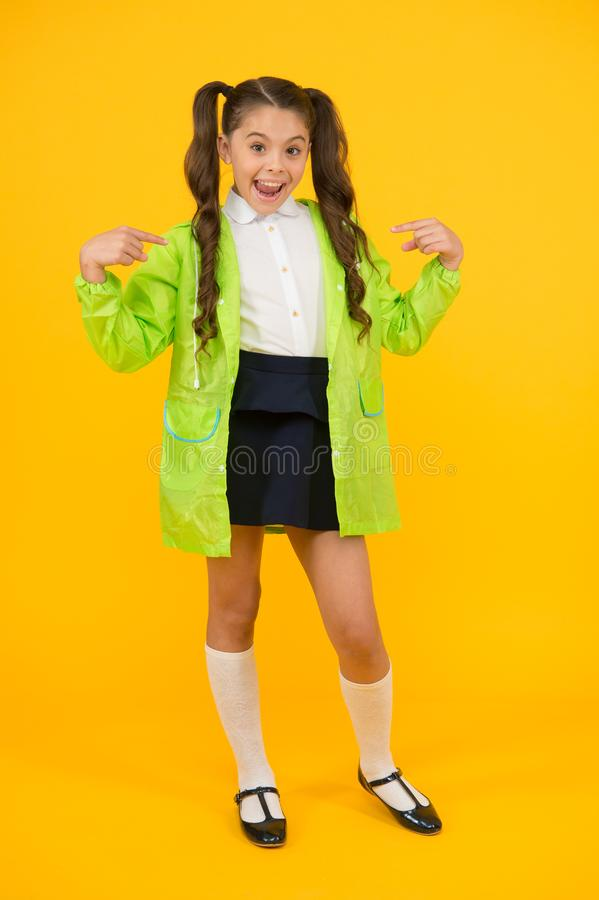 Protecting your child in a rainy day. Happy child pointing at rain poncho on yellow background. Little child back to stock photo