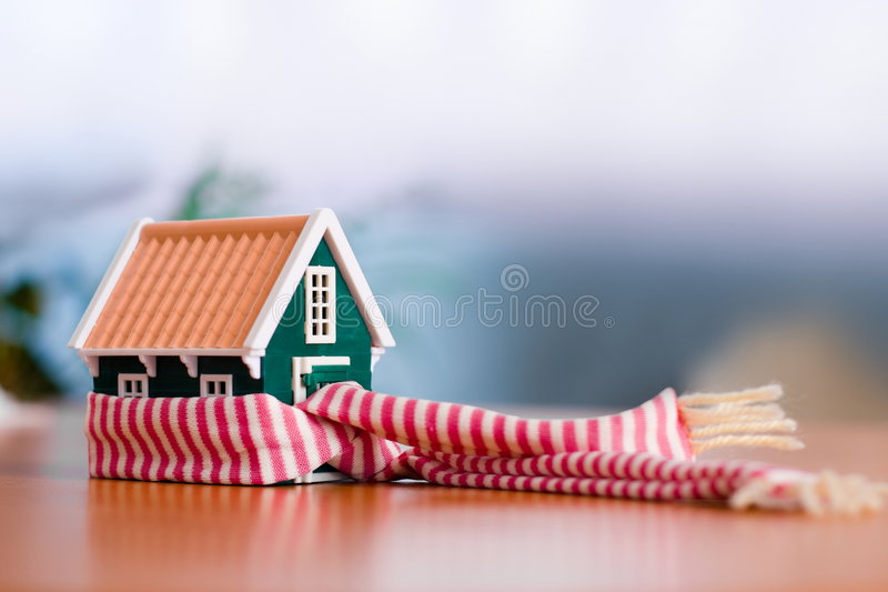 Protecting your house. Scarf around a miniature green house - conceptual view of protecting or isolating house royalty free stock photos