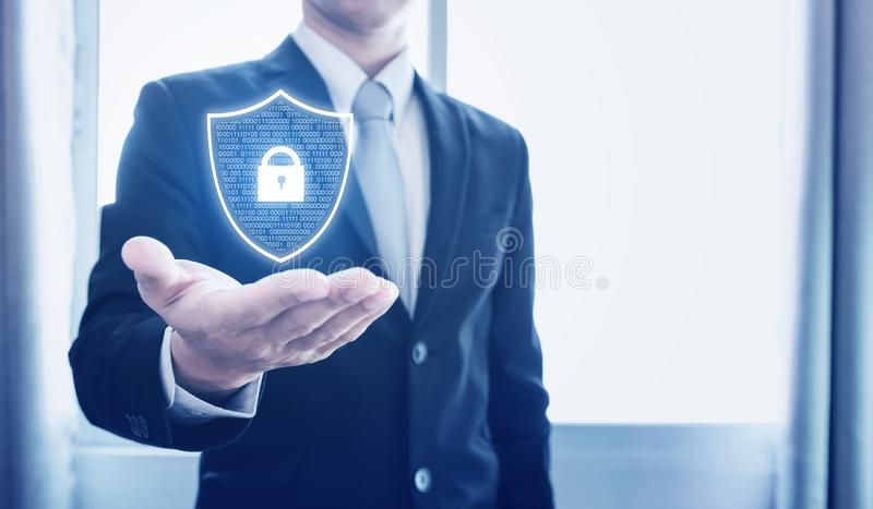 Protection business network and digital data. Businessman holding shield with lock icon stock image