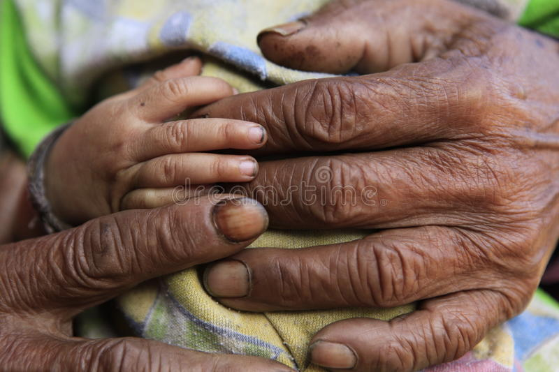 Protection. Old hand and young hand holding royalty free stock photo