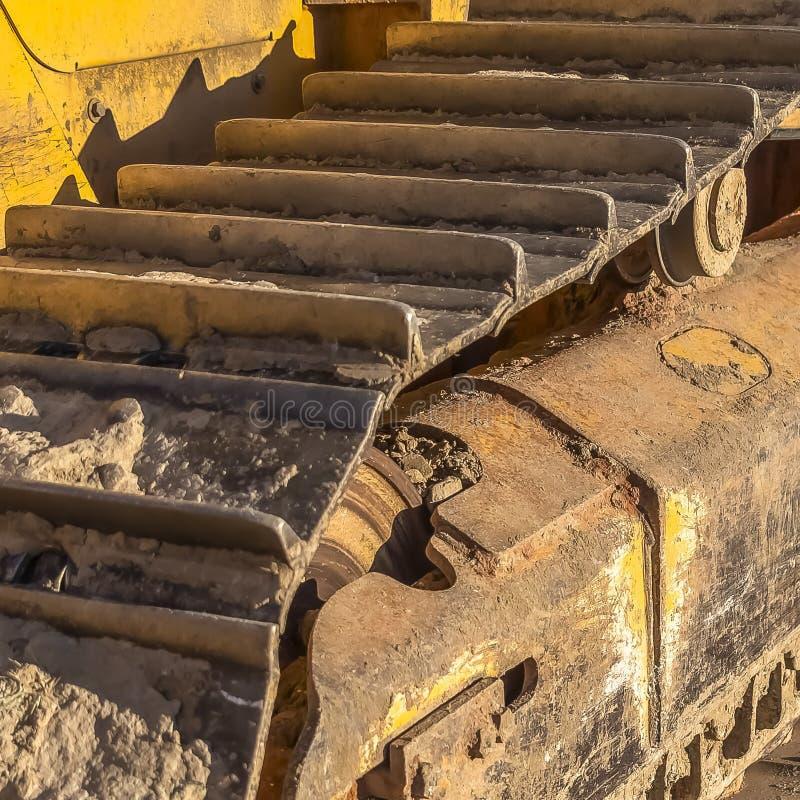 Protection sale de voie en métal de place des machines de construction jaunes un jour ensoleillé photographie stock libre de droits