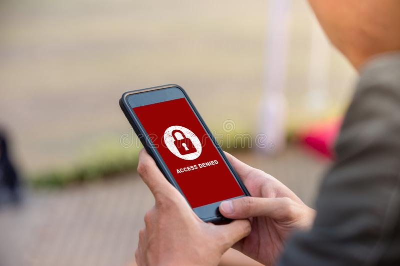 Your access is denied on smartphone screen concept, protection security system. Protection security system concept. Man holding smartphone with access denied royalty free stock photos