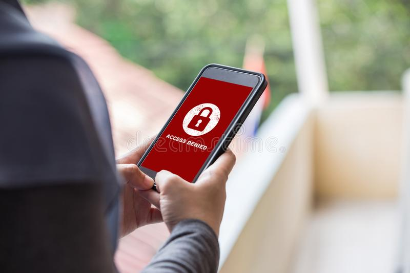 Your access is denied on smartphone screen concept, protection security system. Protection security system concept. Woman holding smartphone with access denied stock photo