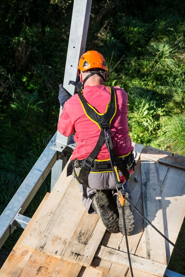 Fall protection. Balcony assembly. Manual worker in seat harness. Workman with orange helmet when building metal framework. Belaying on rope. Height work stock photography