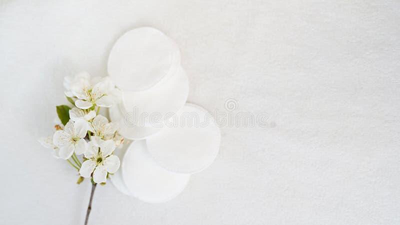 Protections cosm?tiques hygi?niques et fleur de produit jetable sur le fond blanc avec l'espace de copie Concept de soin de corps image libre de droits
