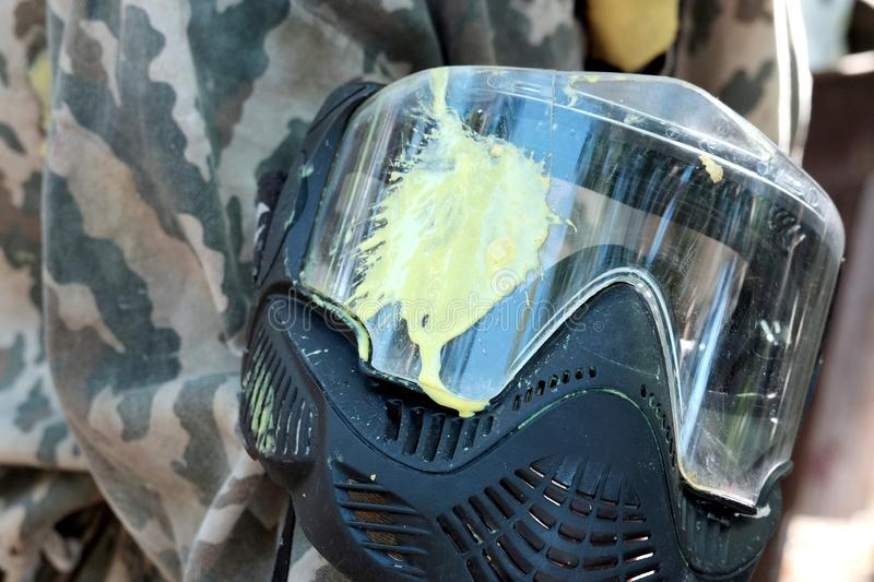 Protective black mask with a yellow blot on the glass. Paintball. Camouflage background. Sports lifestyle, entertainment, hobbies. Paintball. Protective black stock photo
