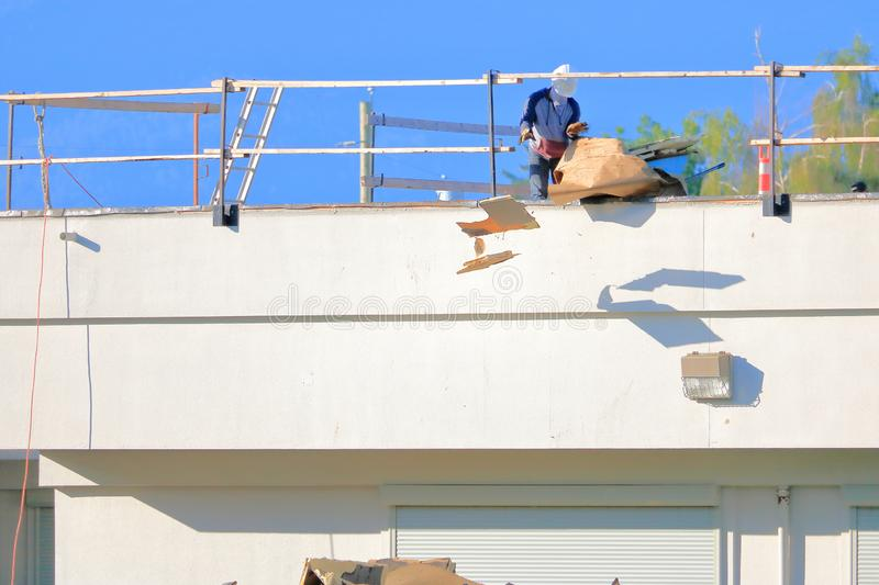 Protective Clothing for Dangerous Construction Material. Scraps of material is thrown off of a building roof while the roofer wears a mask to protect him against stock photo