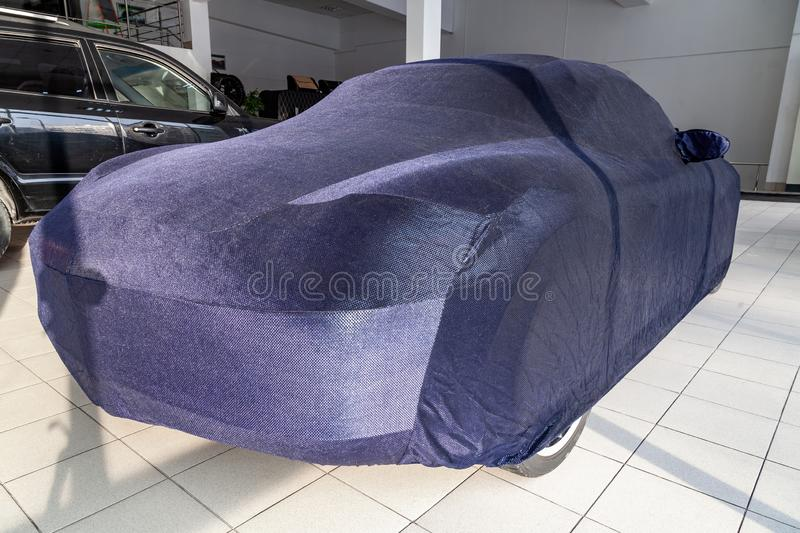 Protective cover awning for cars, blue, made from special material, bespoke at the auto repair shop, covering an expensive sports. Car, prepared for winter stock images