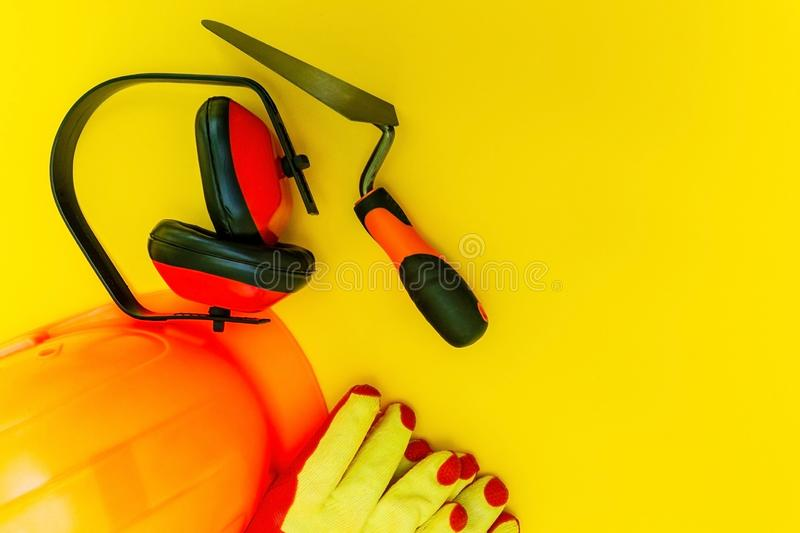 Protective equipment and tools in a bag for the builder on a yellow background stock images