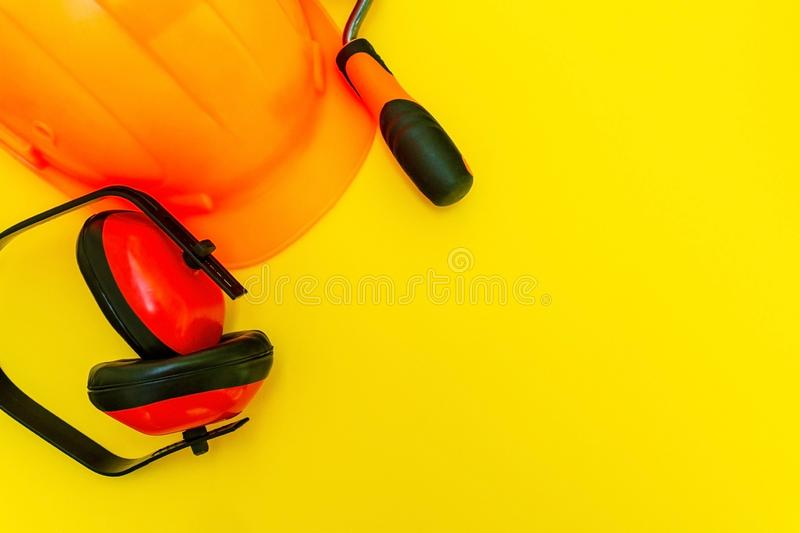 Protective equipment and tools in a bag for the builder on a yellow background royalty free stock image