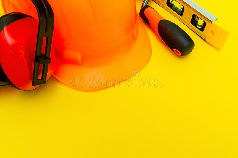 Protective equipment and tools in a bag for the builder on a yellow background royalty free stock photography