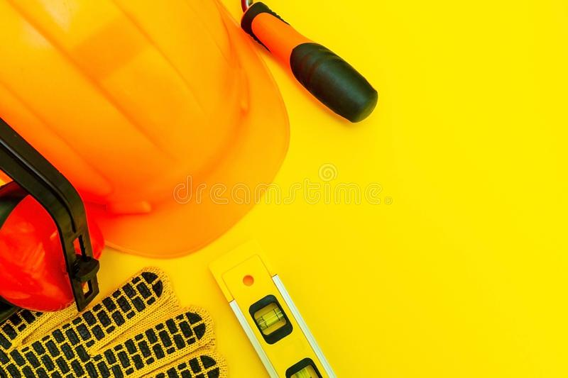 Protective equipment and tools in a bag for the builder on a yellow background royalty free stock images