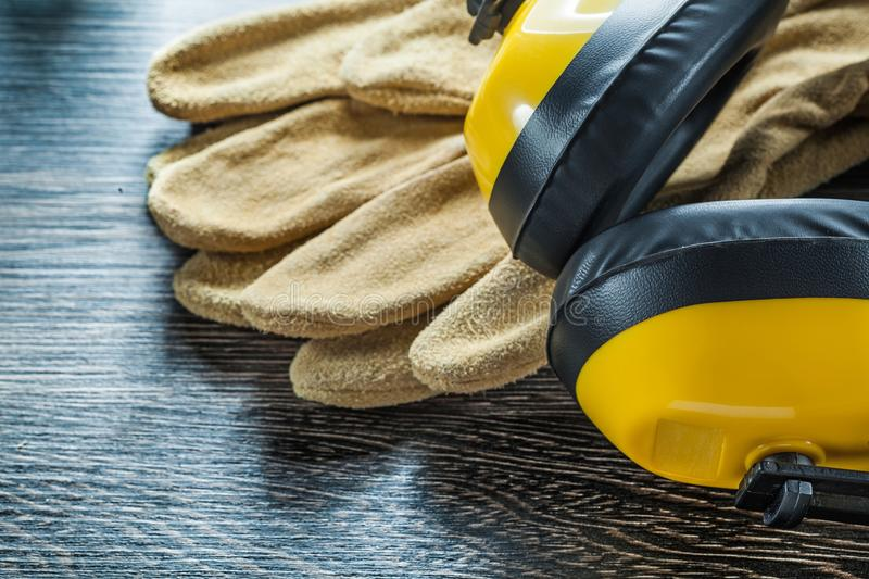 Protective gloves noise reduction earmuffs on black board.  stock image