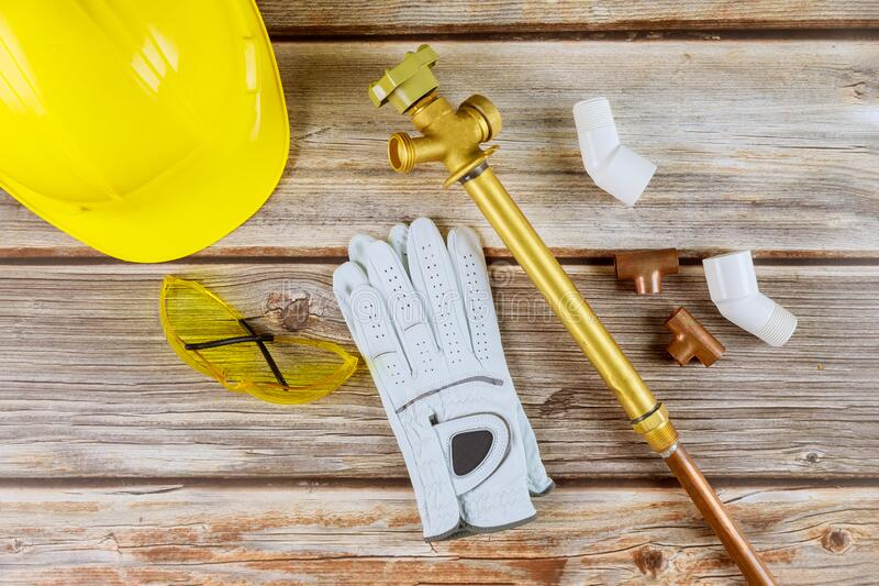 Protective hard work gloves on yellow hard-hat, copper pipes, safety glasses. Protective hard work gloves on yellow hard hat, copper pipes, safety glasses royalty free stock photos
