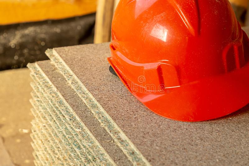 Protective helmet bright orange worker safety, construction design lies on a plywood sheet royalty free stock photography