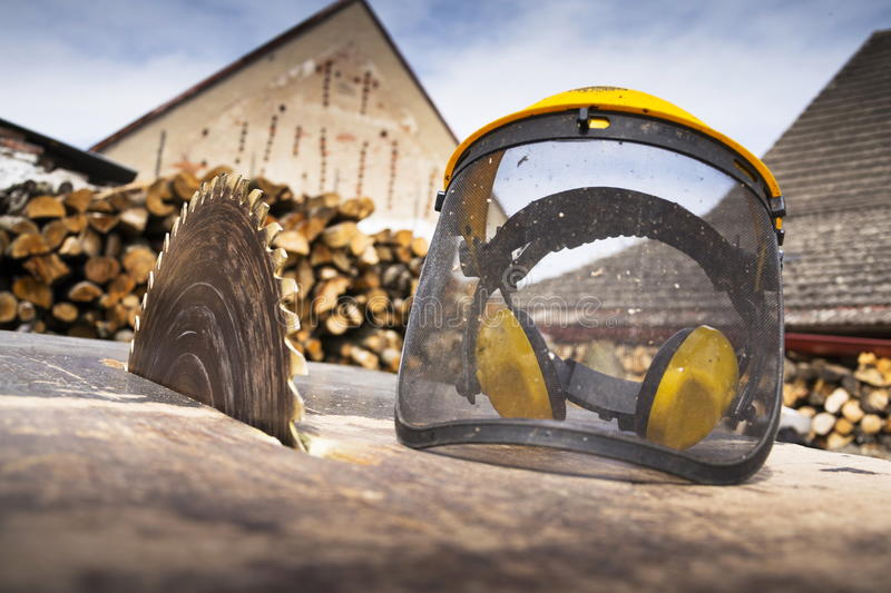 Protective helmet on switched off old rusty circular saw stock photography