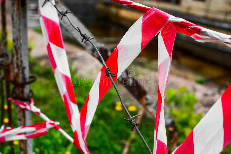Protective red tape and barbed wire stock images