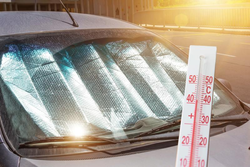 Protective reflective surface under the windshield of the passenger car parked on a hot day, heated by the sun`s rays. The stock photos