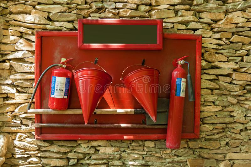 Protective shield with a tool for firemen. A protective shield with a tool for firemen: buckets, shovel, fire extinguishers, scrap.Protective shield with a tool royalty free stock image