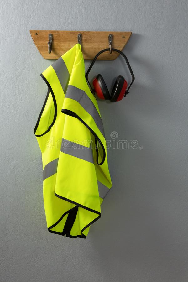 Protective workwear and earmuffs hanging on hook stock images