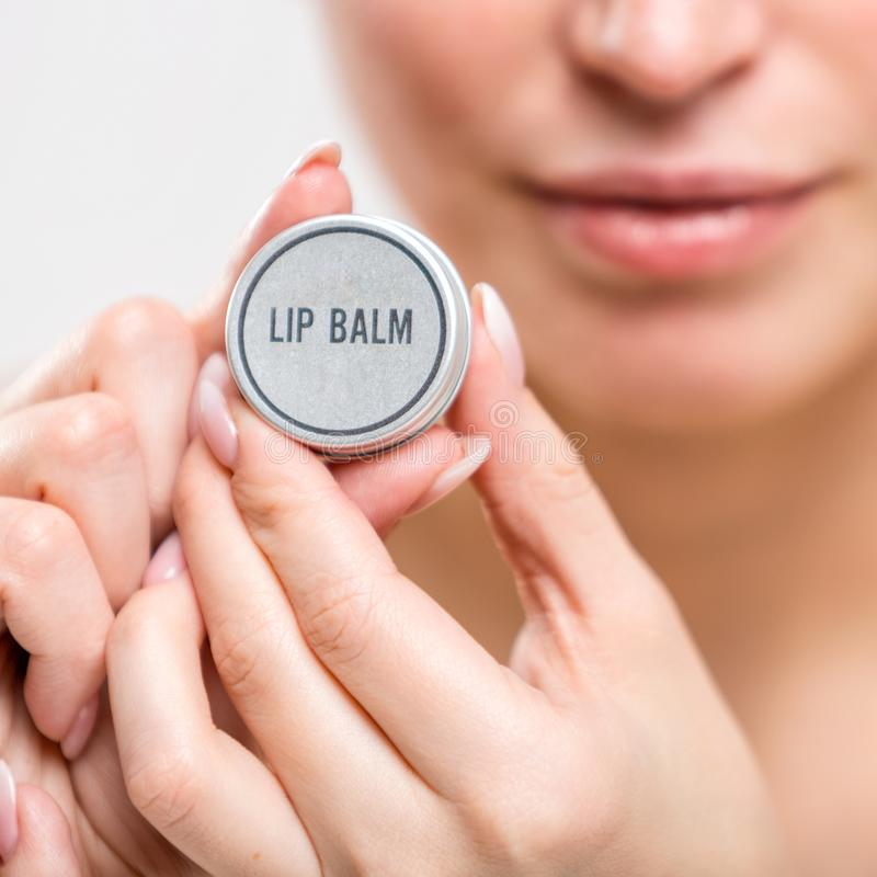 Protector labial Producto cosmético en manos femeninas foto de archivo