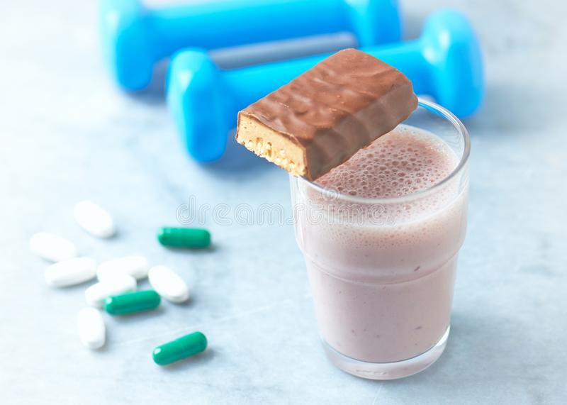 Protein bar, glass of protein shake with milk and raspberries. BCAA amino acids, L - Carnitine capsules and blue dumbbells in back. Ground. Sport nutrition royalty free stock photo