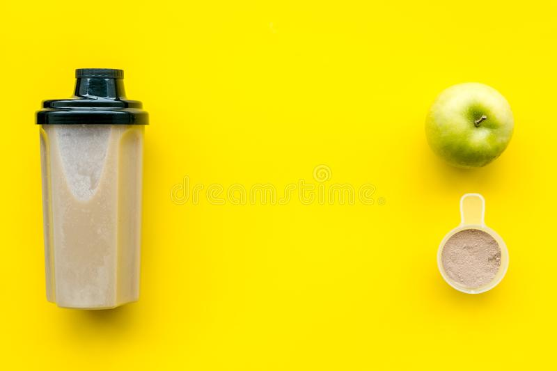 Protein cocktail with powder for sport nutrition set l on yellow background top view mock-up royalty free stock photography