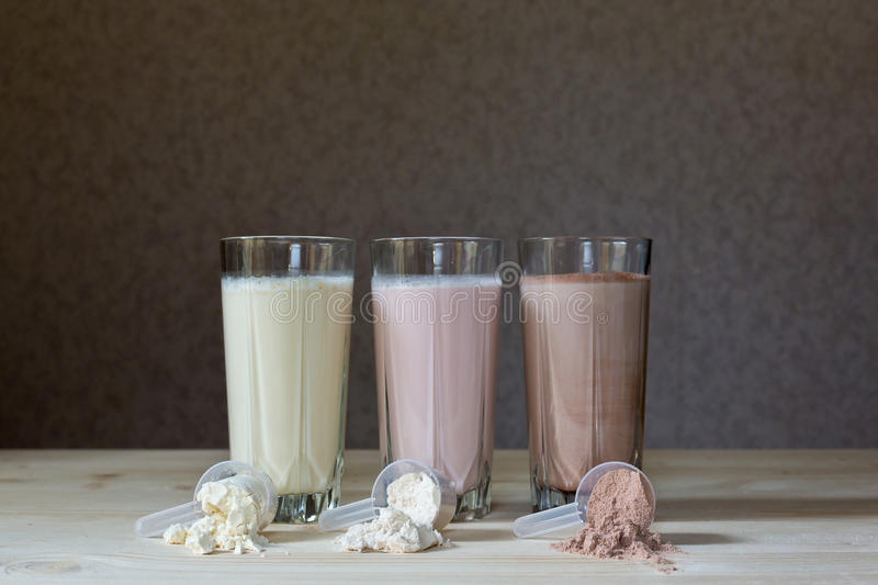 Protein cocktails. Fresh milk, chocolate, blueberry and banana drinks on table, assorted protein cocktails royalty free stock images