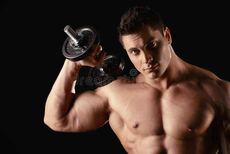 Protein diet. Portrait of a handsome muscular bodybuilder posing with dumbbells over black background stock images
