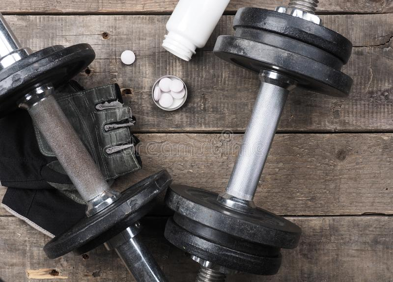Protein pills with dumbbells on wood, top view stock photography