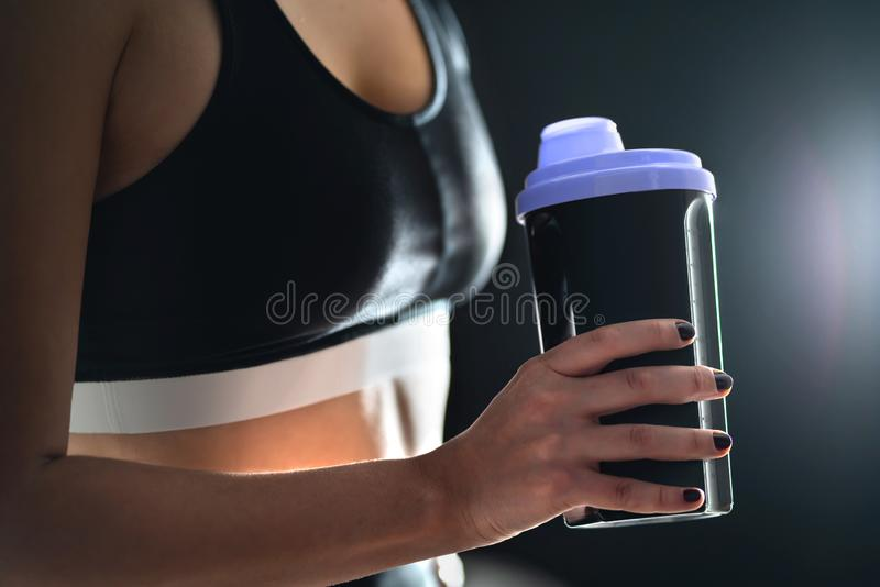 Protein shake after workout and gym training. Fit woman holding bottle of sport drink, whey or healthy smoothie. Fitness athlete with shaker. Drinking royalty free stock photo